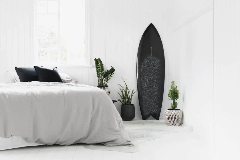 minimalist bedroom with surfboard